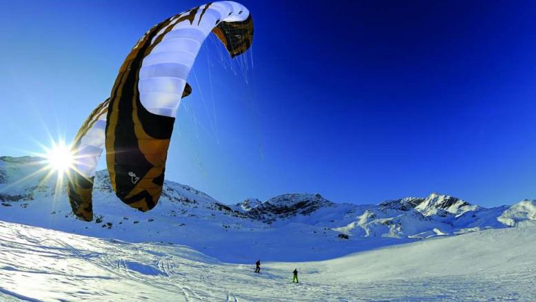 txn-p. Snow Kiten ist ein Wintersport der etwas anderen Art. Auf Skiern oder Snowboards flitzen Actionfans an Lenkdrachen über vereiste Schneefelder. Foto: stipi/Fotolia/jochen-schweizer.de