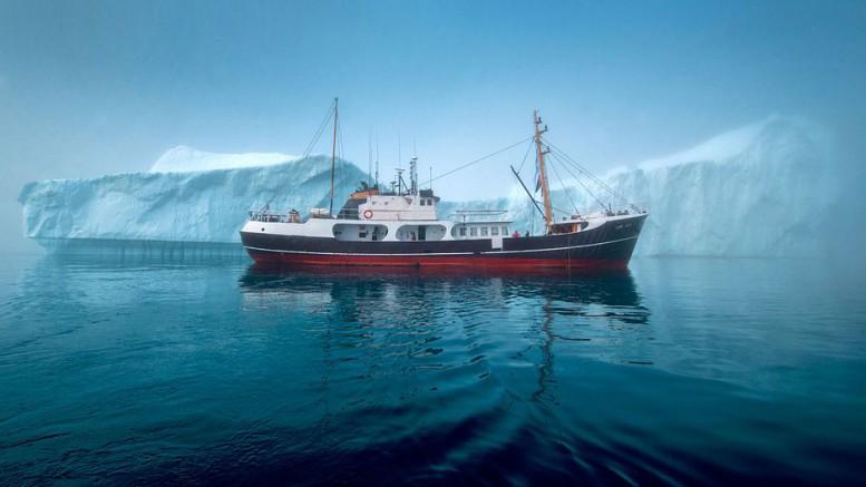 """Im Vergleich zu den Eisbergen der Diskobucht sieht die knapp 34 Meter lange """"Cape Race"""" klein aus. Foto: djd/Polar Kreuzfahrten"""